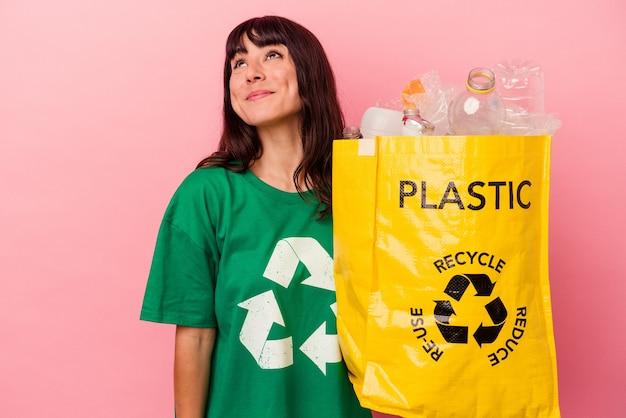 Jonge kaukasische vrouw die een gerecycleerde plastic zak houdt die op roze achtergrond wordt geïsoleerd en droomt van het bereiken van doelstellingen en doeleinden