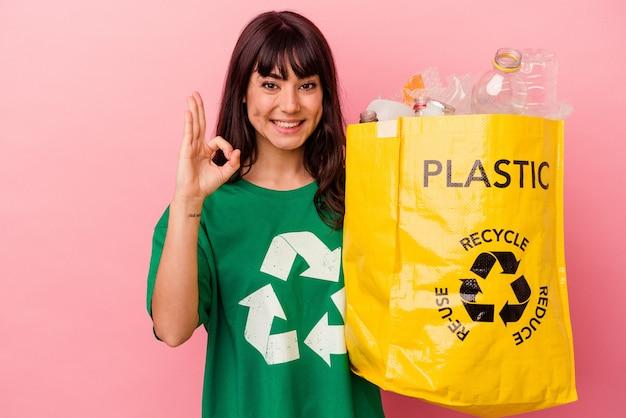 Jonge kaukasische vrouw die een gerecycleerde plastic zak houdt die op roze vrolijke en zelfverzekerde achtergrond wordt geïsoleerd die ok gebaar toont.