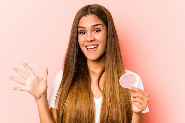 Jonge kaukasische vrouw die een gezichtsspons houdt die een overwinning of een succes viert