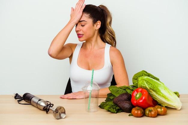 Jonge kaukasische vrouw die een gezonde smoothie met groenten voorbereidt die iets vergeten, voorhoofd met handpalm slaan en ogen sluiten.