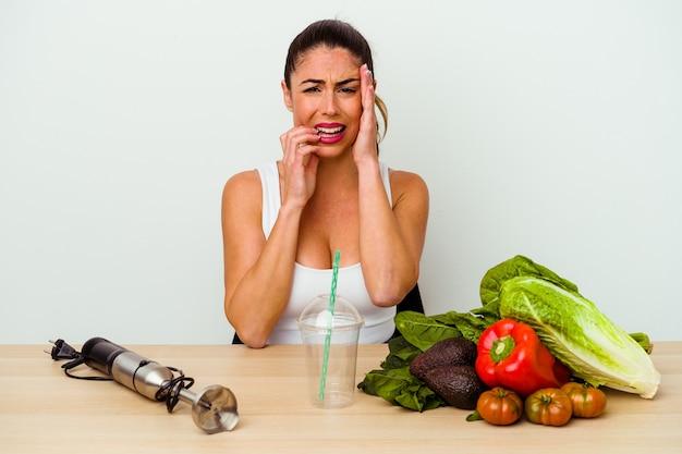 Jonge kaukasische vrouw die een gezonde smoothie met groenten voorbereidt die troosteloos jammeren en huilen.