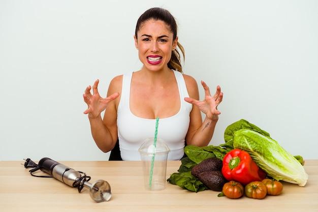 Jonge kaukasische vrouw die een gezonde smoothie met groenten voorbereidt die van woede gillen.