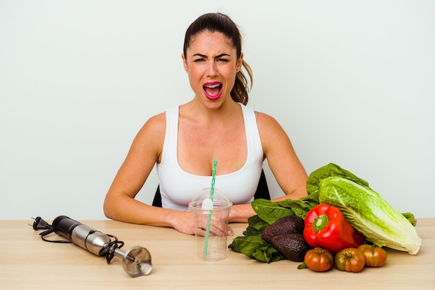Jonge kaukasische vrouw die een gezonde smoothie met groenten voorbereidt die zeer boos en agressief gillen.