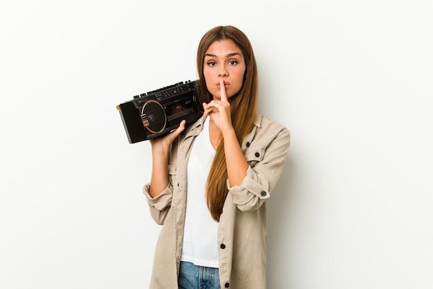 Jonge kaukasische vrouw die een guettoblaster houdt die een geheim houdt of om stilte vraagt.