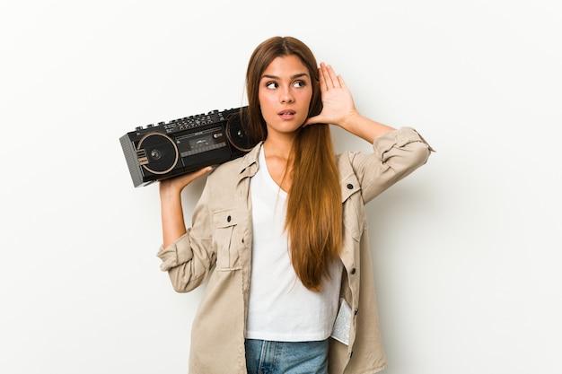 Jonge kaukasische vrouw die een guettoblaster houdt die een roddel probeert te luisteren.