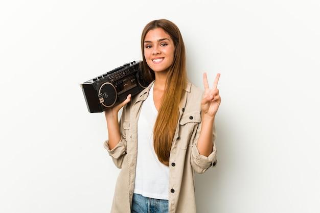 Jonge kaukasische vrouw die een guettoblaster houdt die nummer twee met vingers toont.