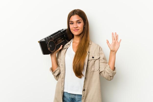 Jonge kaukasische vrouw die een guettoblaster houdt die vrolijk tonend nummer vijf met vingers glimlacht.