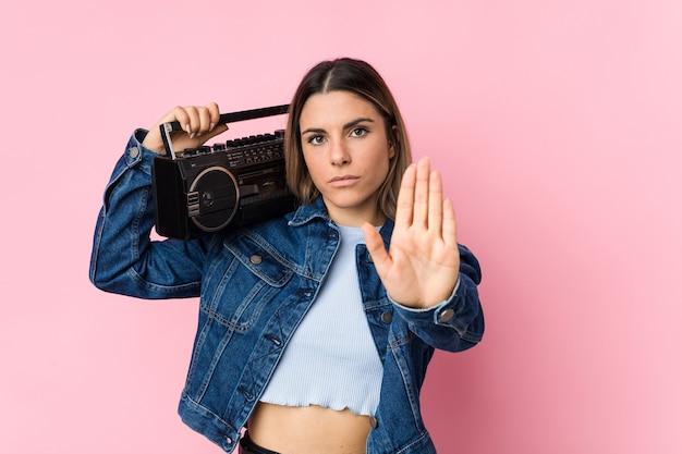 Jonge kaukasische vrouw die een guettoblaster houdt die zich met uitgestrekte hand bevindt die stopbord toont, dat u verhindert.