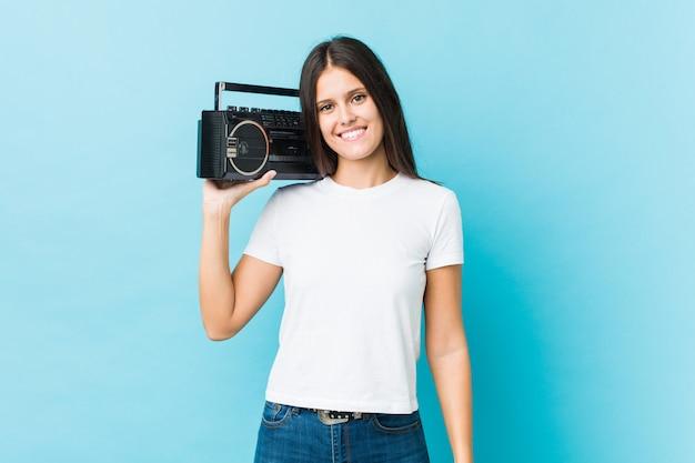 Jonge kaukasische vrouw die een guettoblaster houdt, glimlachend en vrolijk.