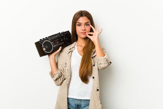 Jonge kaukasische vrouw die een guettoblaster met vingers op lippen houdt die een geheim houdt.