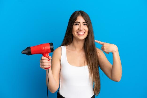 Jonge kaukasische vrouw die een haardroger houdt die op blauwe achtergrond wordt geïsoleerd en een duim omhoog gebaar geeft