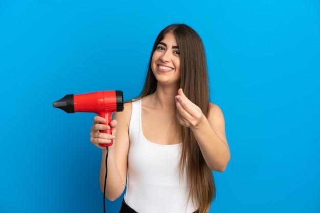 Jonge kaukasische vrouw die een haardroger houdt die op blauwe achtergrond wordt geïsoleerd en geldgebaar maakt
