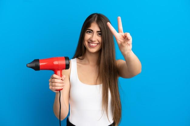 Jonge kaukasische vrouw die een haardroger houdt die op blauwe achtergrond wordt geïsoleerd en glimlacht en overwinningsteken toont