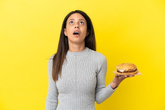 Jonge kaukasische vrouw die een hamburger houdt die op gele achtergrond wordt geïsoleerd en omhoog kijkt en met verbaasde uitdrukking