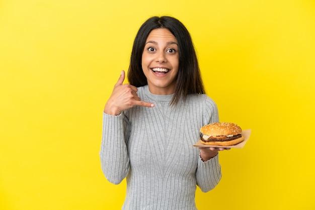Jonge kaukasische vrouw die een hamburger houdt die op gele achtergrond wordt geïsoleerd en telefoongebaar maakt. bel me terug teken