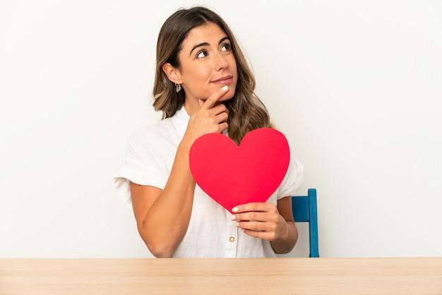 Jonge kaukasische vrouw die een hart van de valentijnskaartendag houdt