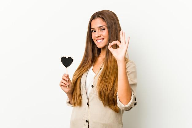 Jonge kaukasische vrouw die een hartvorm vrolijk en zeker houdt die ok gebaar toont.
