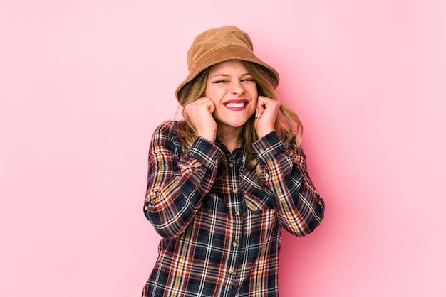 Jonge kaukasische vrouw die een hoed draagt die oren behandelt met handen.
