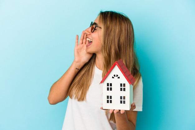 Jonge kaukasische vrouw die een huismodel houdt dat op blauwe achtergrond wordt geïsoleerd die en palm dichtbij geopende mond houdt.