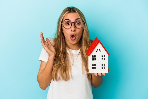 Jonge kaukasische vrouw die een huismodel houdt dat op blauwe achtergrond wordt geïsoleerd verrast en geschokt.