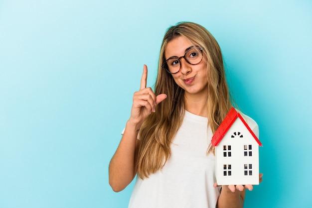 Jonge kaukasische vrouw die een huismodel houdt dat op blauwe muur wordt geïsoleerd die nummer één met vinger toont