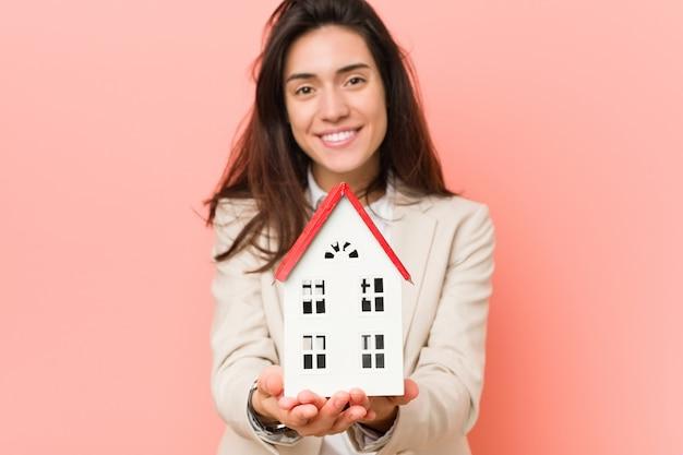 Jonge kaukasische vrouw die een huismodel houdt