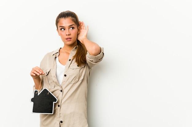 Jonge kaukasische vrouw die een huispictogram houdt dat aan een roddel probeert te luisteren.