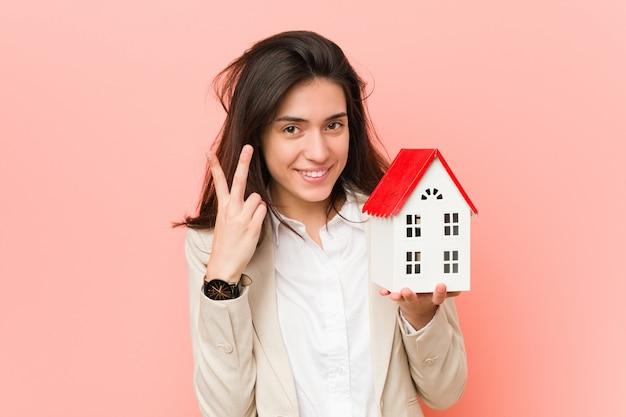 Jonge kaukasische vrouw die een huispictogram houdt