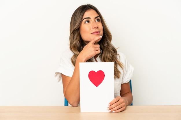 Jonge kaukasische vrouw die een kaart van de valentijnskaartendag houdt