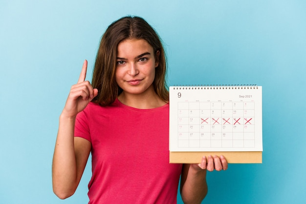 Jonge kaukasische vrouw die een kalender houdt die op roze achtergrond wordt geïsoleerd die nummer één met vinger toont.