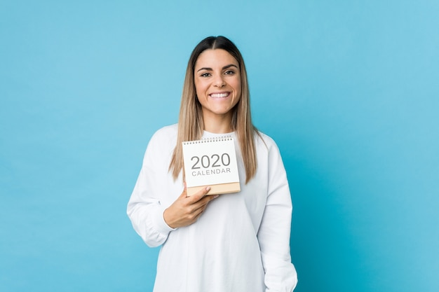 Jonge kaukasische vrouw die een kalender van 2020 gelukkig, glimlachend en vrolijk houdt.
