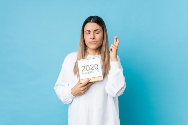 Jonge kaukasische vrouw die een kalender van 2020 houdt die vingers kruist voor het hebben van geluk
