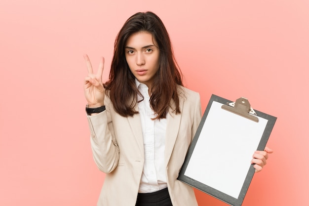Jonge kaukasische vrouw die een klembord houdt