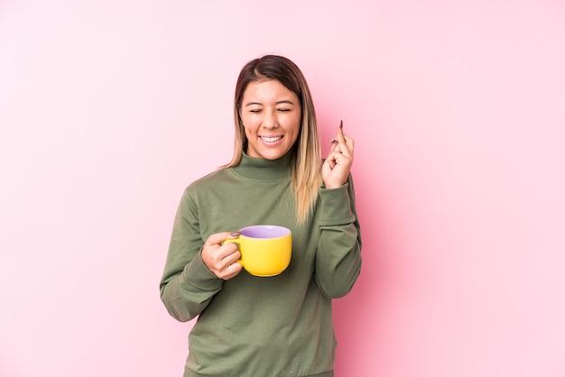 Jonge kaukasische vrouw die een koffie houdt die vingers kruist