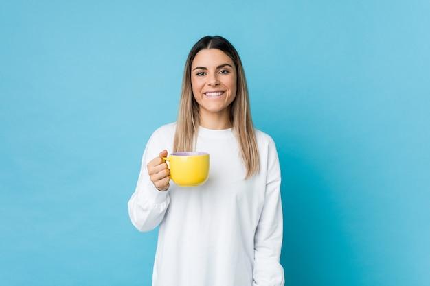 Jonge kaukasische vrouw die een koffiekop gelukkig, glimlachend en vrolijk houdt.