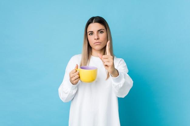 Jonge kaukasische vrouw die een koffiekop houdt die nummer één met vinger toont.