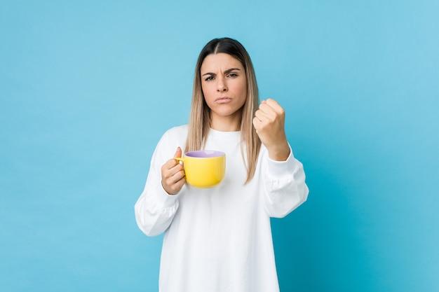 Jonge kaukasische vrouw die een koffiekop houdt die vuist toont aan camera, agressieve gelaatsuitdrukking.