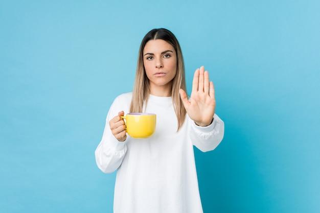 Jonge kaukasische vrouw die een koffiekop houdt die zich met uitgestrekte hand bevindt die eindeteken toont, dat u verhindert.