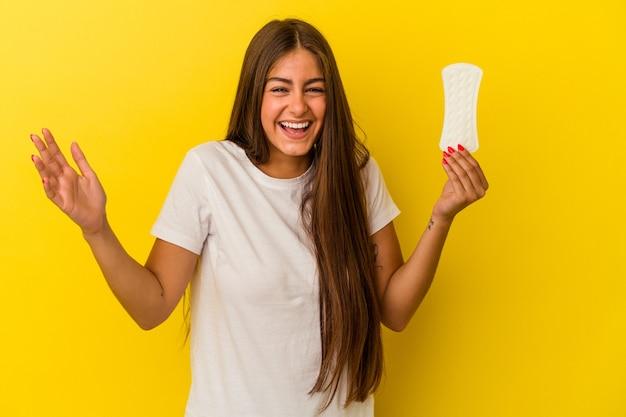 Jonge kaukasische vrouw die een kompres houdt dat op gele achtergrond wordt geïsoleerd en een aangename verrassing ontvangt, opgewonden en handen opsteekt.
