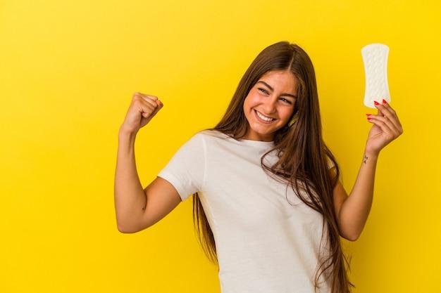 Jonge kaukasische vrouw die een kompres houdt dat op gele achtergrond wordt geïsoleerd en vuist opheft na een overwinning, winnaarconcept.