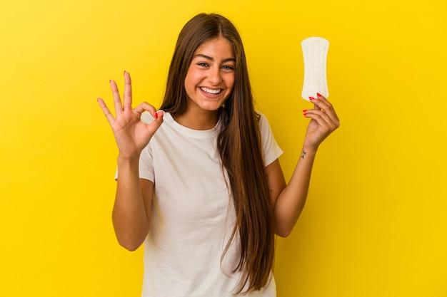 Jonge kaukasische vrouw die een kompres houdt dat op gele achtergrond wordt geïsoleerd, vrolijk en zelfverzekerd met een goed gebaar.