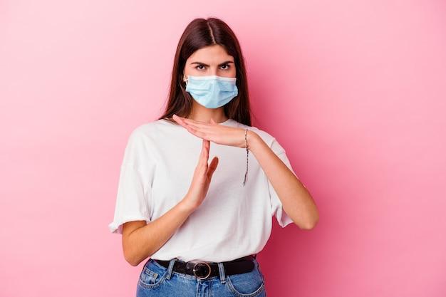 Jonge kaukasische vrouw die een masker voor virus draagt dat op roze muur wordt geïsoleerd die een onderbrekingsgebaar toont