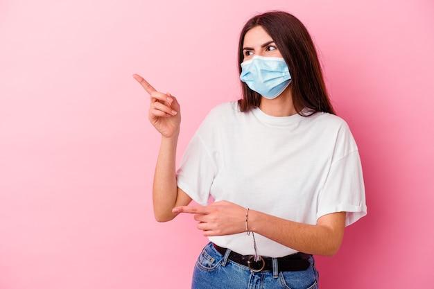 Jonge kaukasische vrouw die een masker voor virus draagt dat op roze muur wordt geïsoleerd opgewonden richtend met weg wijsvingers
