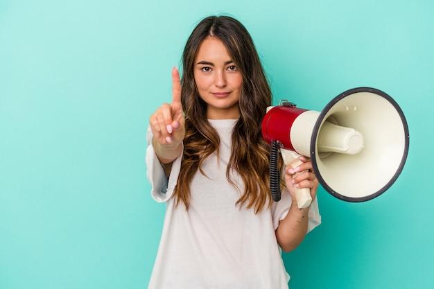 Jonge kaukasische vrouw die een megafoon houdt die op blauwe achtergrond wordt geïsoleerd die nummer één met vinger toont.