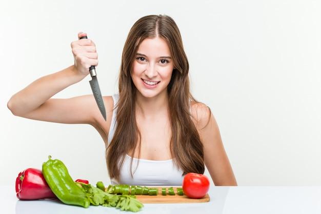 Jonge kaukasische vrouw die een mes houdt en groenten snijdt