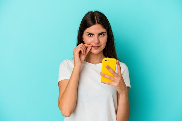 Jonge kaukasische vrouw die een mobiele telefoon houdt die op blauwe achtergrond met vingers op lippen wordt geïsoleerd die een geheim houden.