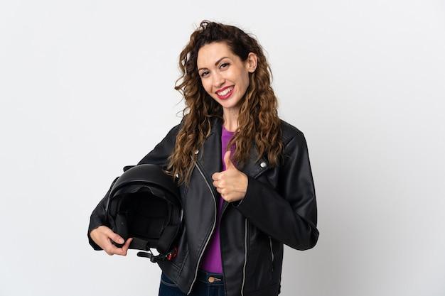 Jonge kaukasische vrouw die een motorhelm houdt die een duimen op gebaar geeft