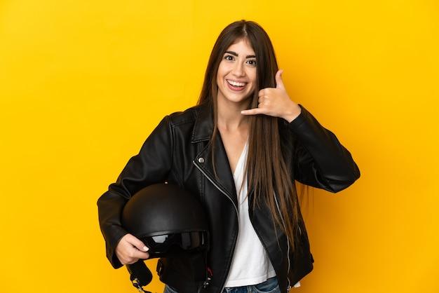 Jonge kaukasische vrouw die een motorhelm houdt die op gele muur wordt geïsoleerd die telefoongebaar maakt. bel me terug teken