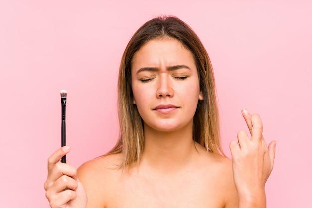 Jonge kaukasische vrouw die een oogborstel houdt die vingers kruist
