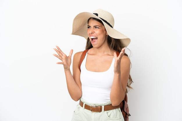 Jonge kaukasische vrouw die een pamela draagt in de zomervakantie die op witte achtergrond met verrassingsgelaatsuitdrukking wordt geïsoleerd
